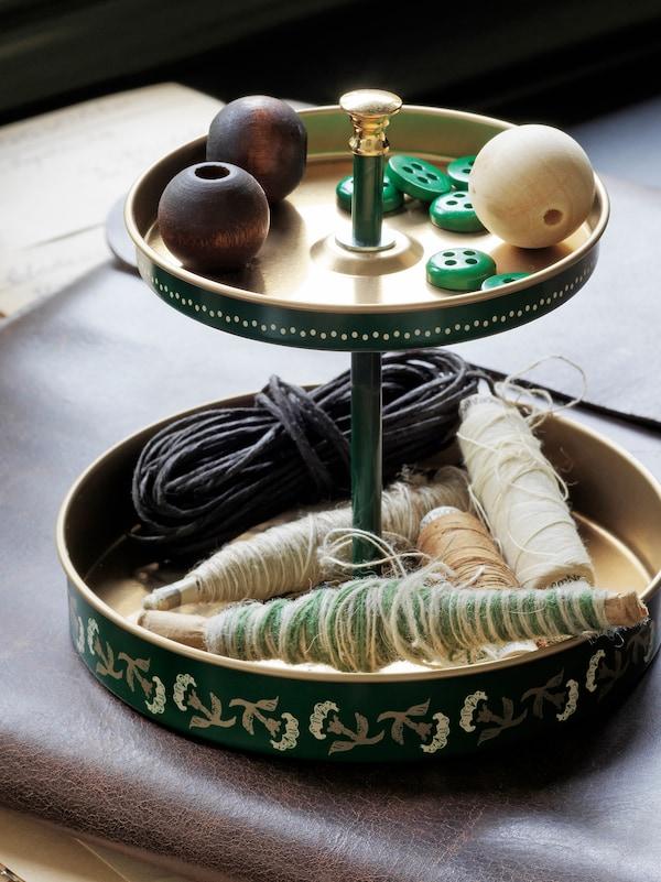 桌上放着双层办公桌收纳件,里面放着各式钮扣、线团、还有大颗的手工木珠。