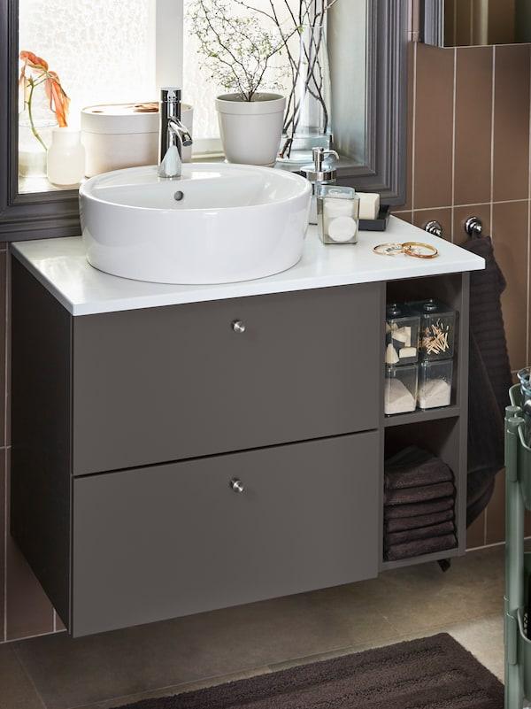 Conxunto de lavabo e moble de soporte en branco e gris escuro, toallas e alfombra de baño marrón escuro.