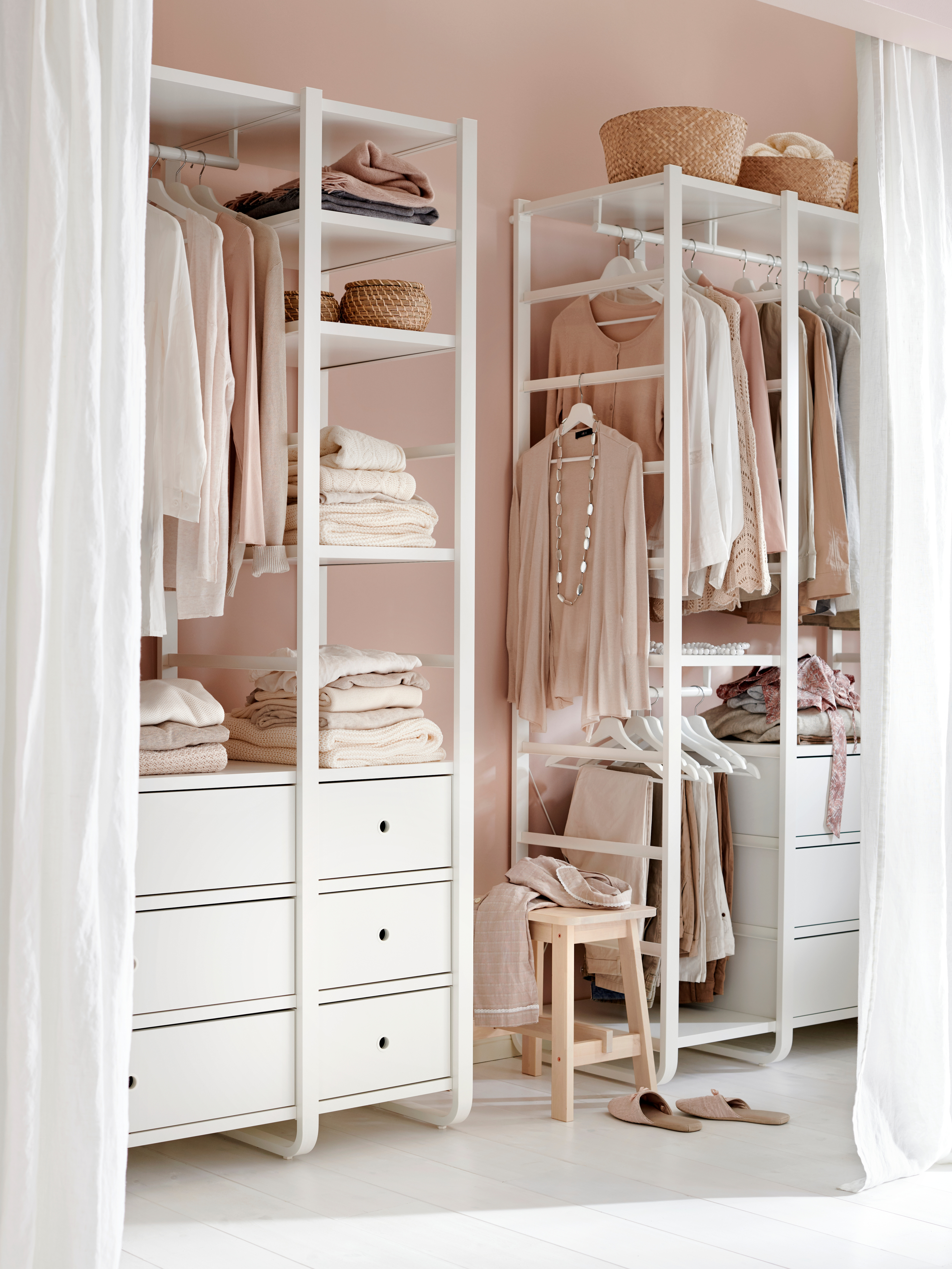 Two, white ELVARLI three-section storage units with drawers are filled with clothes, against a wall with a stool in between.