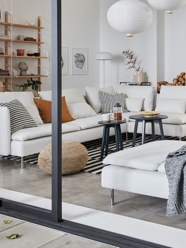 A living room/dining area seen through open patio doors, showing a large SÖDERHAMN sofa and two chaises longues.