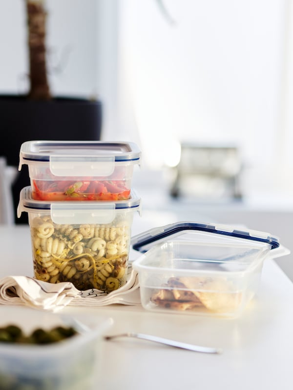 Three small food containers filled with leftovers.