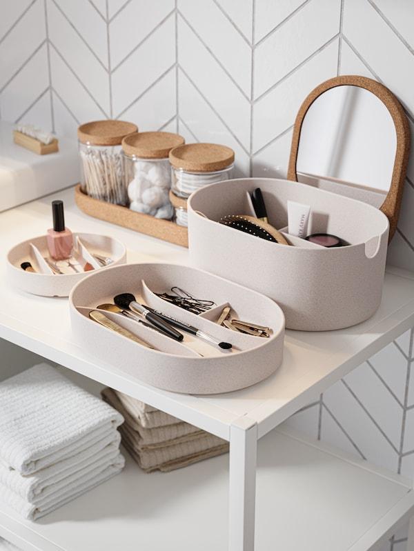 Mesado branco con caixas de almacenaxe da mesma cor con esmalte de uñas, maquillaxe, pinzas do pelo, pinceis e outros accesorios.