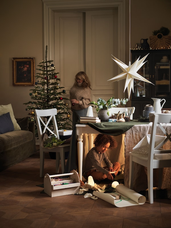 A living room decorated for the winter holiday with a child playing under the dinner table and a woman dressing a tree.
