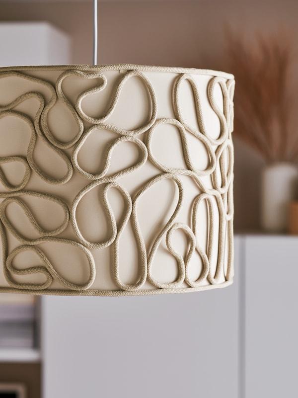 Détails d'une suspension avec abat-jour VINGMAST beige composé de cordons formant des motifs sinueux sur un centre recouvert de textile.
