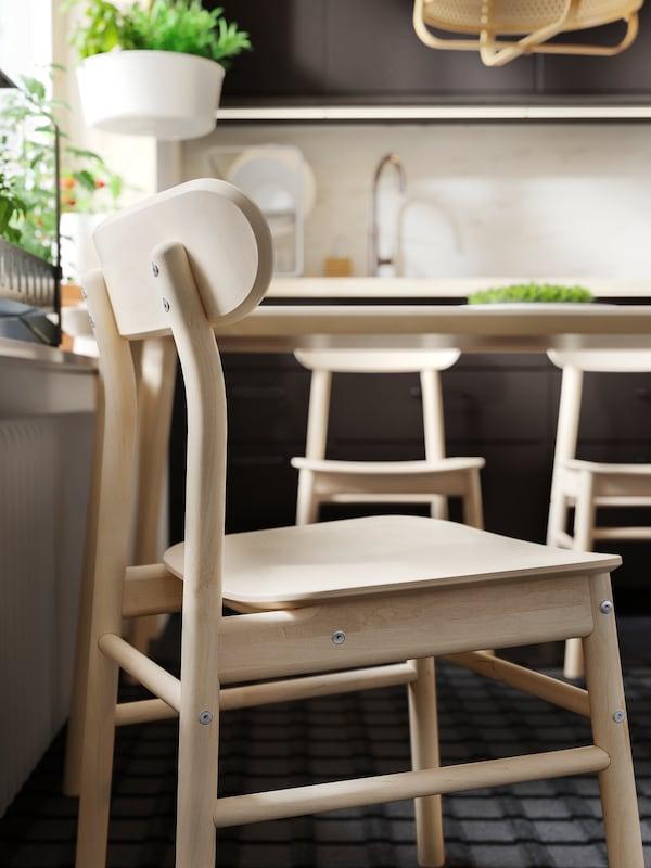 Primer pla d'una cadira RÖNNINGE de bedoll al costat d'una taula LISABO. Al fons hi ha armaris de cuina grisos i unes quantes plantes verdes.