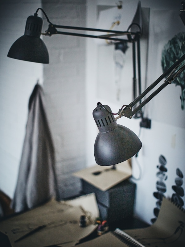 Two dark grey TERTIAL work lamps are mounted on a wall where there are also some illustrations.