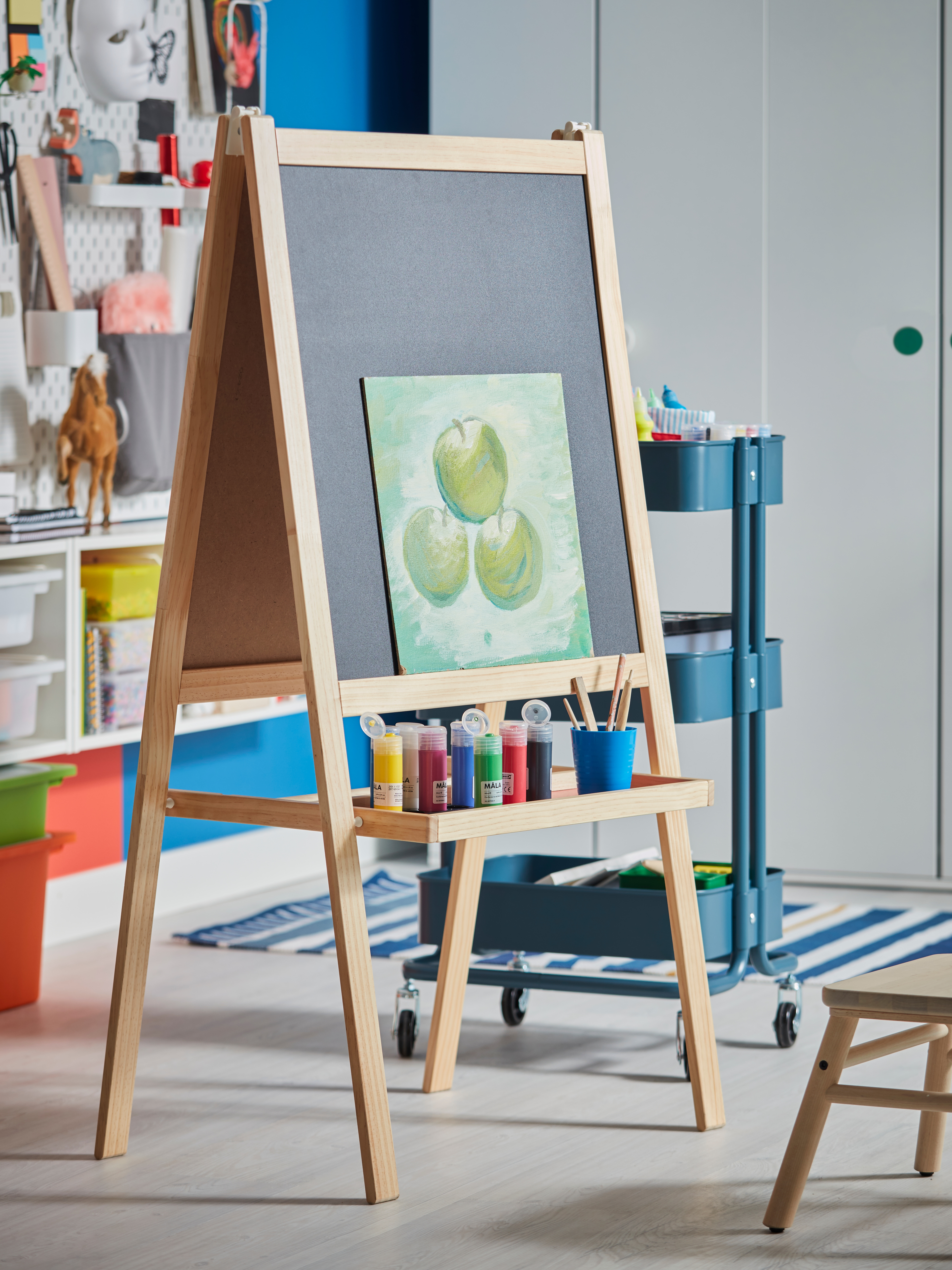 A MÅLA easel in softwood/white with a painting resting on its blackboard side and paint on a tray by a wall of art supplies.