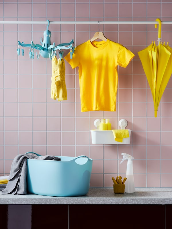 PRESSA hanging dryer and drying, yellow garments hanging from a rod. TISKEN basket and other laundry accessories underneath.