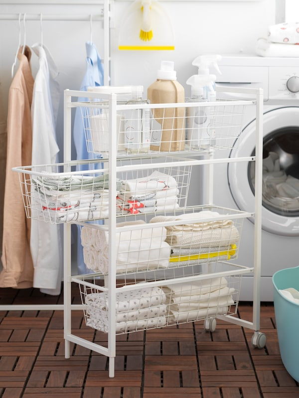 A JONAXEL white frame on castors with mesh baskets full of clean laundry, in front of a washing machine.