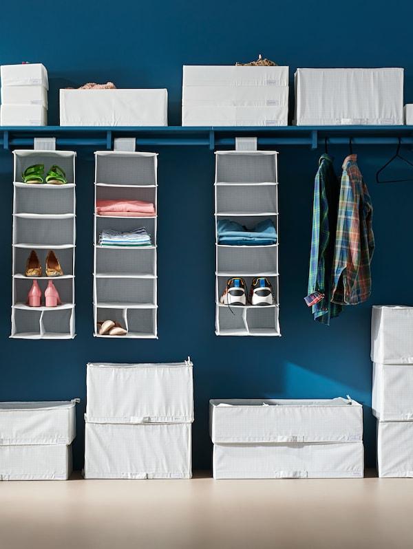 Cutii de depozitare STUK de diferite dimensiuni, în care se află îmbrăcăminte împăturită ordonat, așezate în fața unui perete albastru închis.