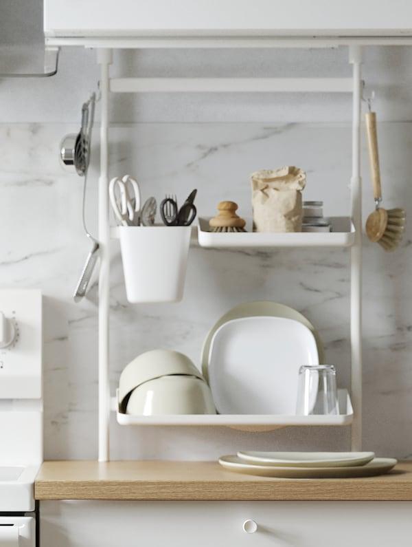Grelha de parede KUNGSFORS em aço inoxidável com gengibre, condimentos e utensílios de cozinha dispostos em recipientes e em ganchos.