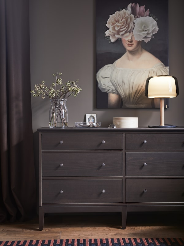 An IDANÄS chest of drawers in dark brown with an EVEDAL table lamp on it, in front of a wall-mounted painting.