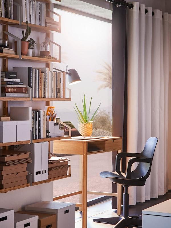 Une chaise noire pivotante devant un bureau en bambou face à une fenêtre ouverte