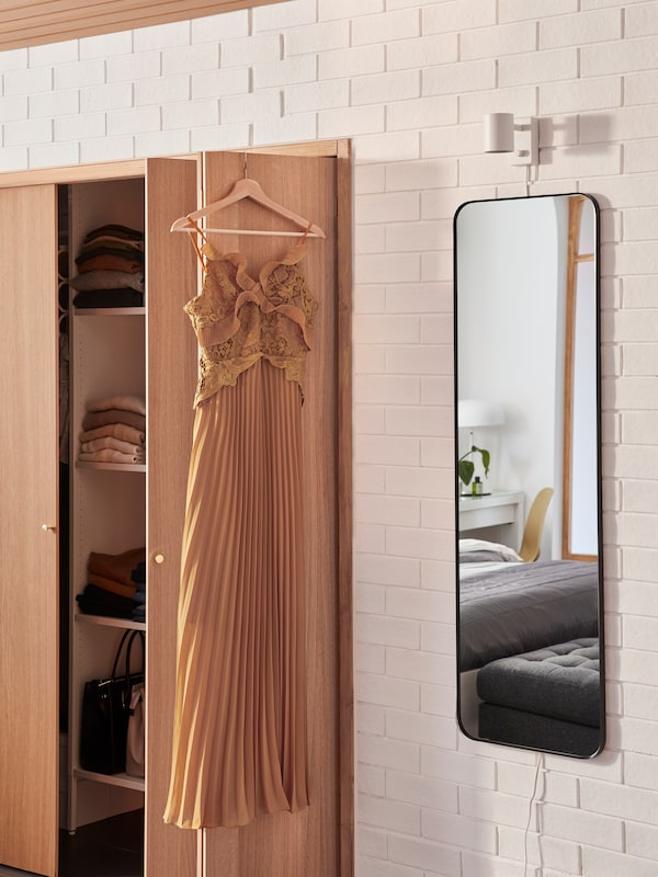 A rectangular LINDBYN mirror with rounded corners is wall-mounted under a NYMÅNE lamp and next to an AURDAL wardrobe.