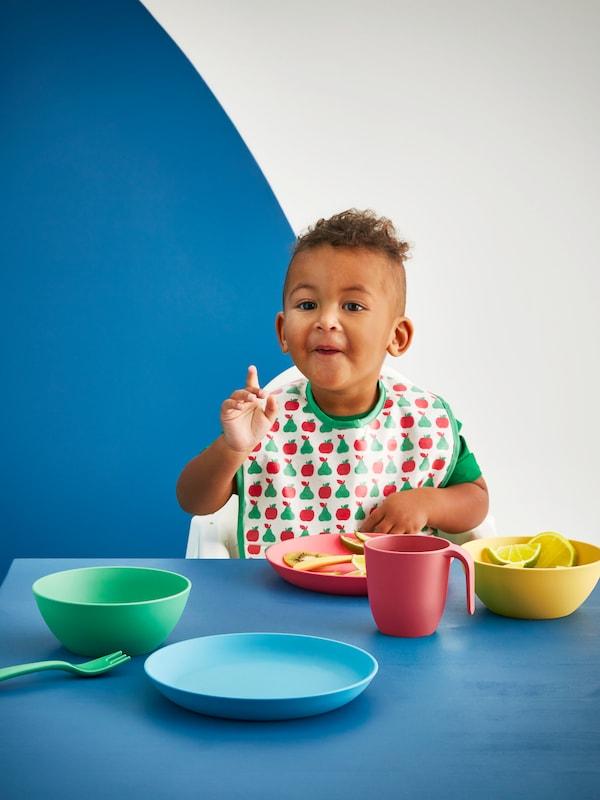 Niño pequeño con un babero MATVRÅ sentado en una trona en una mesa con cuencos, platos, un tazón y cubiertos HEROISK encima.