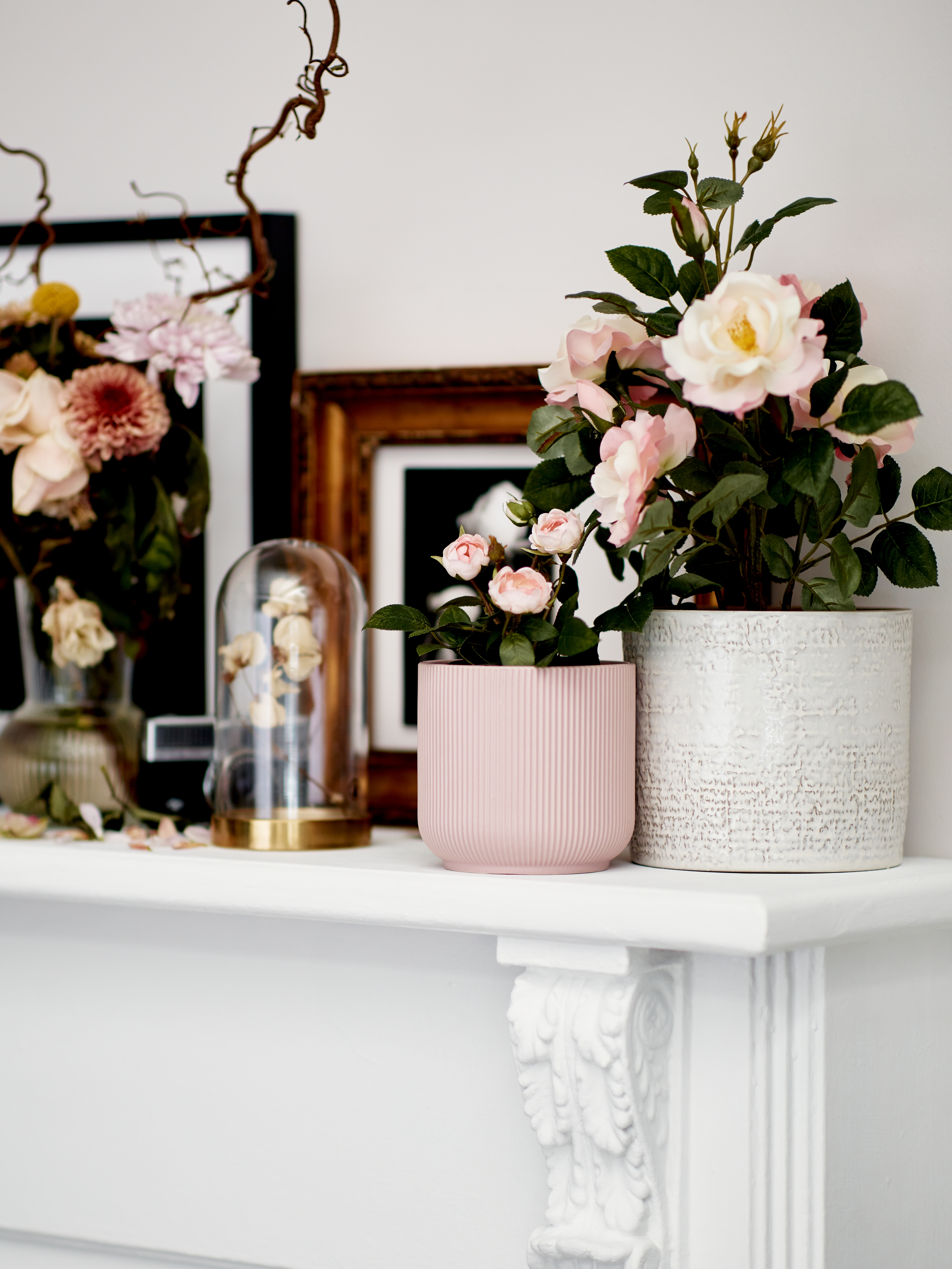 FEJKA artificial flowers in CHIAFRÖN and GRADVIS vases together with framed art and other decorations on a mantelpiece.