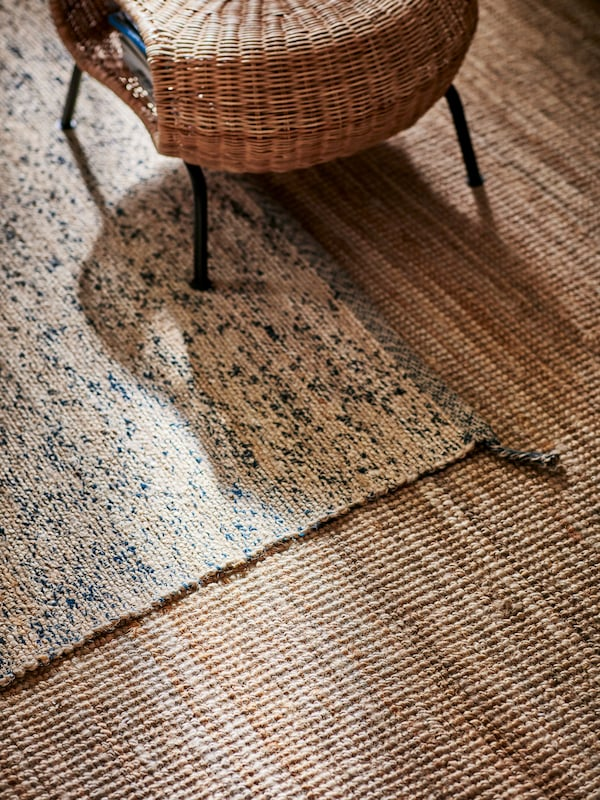 A large jute rug and a smaller jute rug with dark blue wool randomly woven into the jute and a rattan footstool.