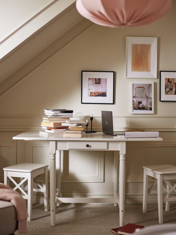 A white INGATORP drop-leaf table with books on the tabletop, by a bright wall with framed pictures and a pink pendant lampshade above.
