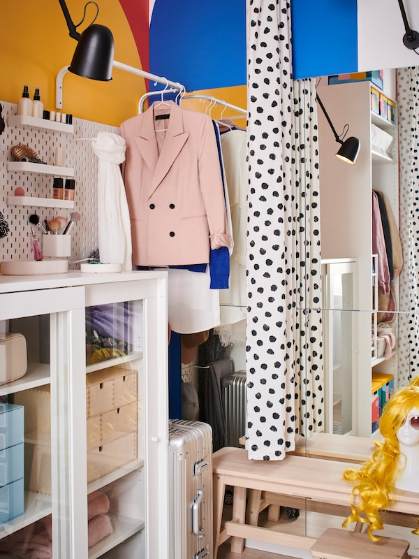 A storage area with a white SYVDE cabinet with boxes inside, clothes rails with hanging clothes and a GO mirror on the wall.