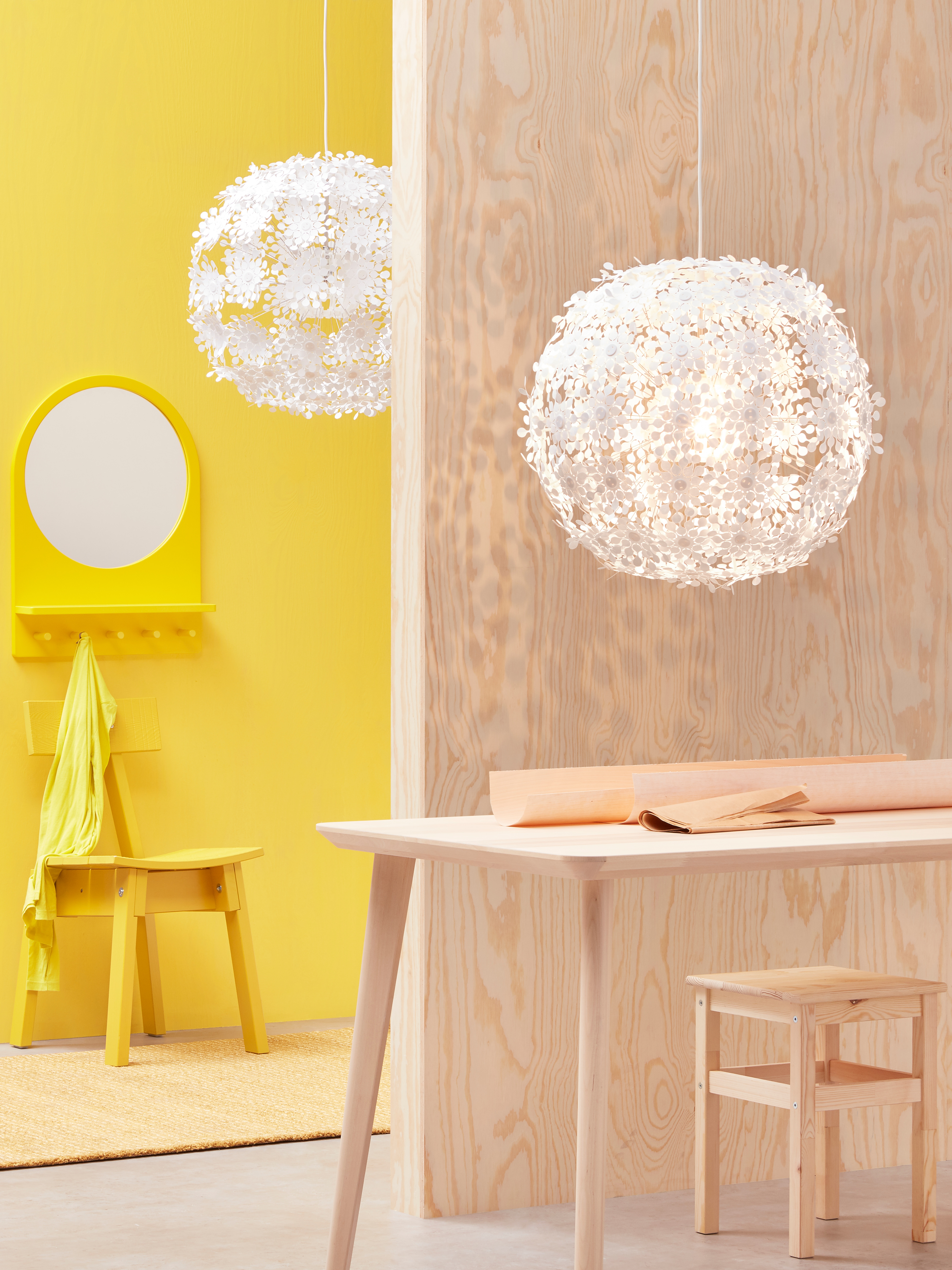 A hallway in the background with a workspace in the foreground, and each has a white GRIMSÅS pendant lamp hanging overhead.