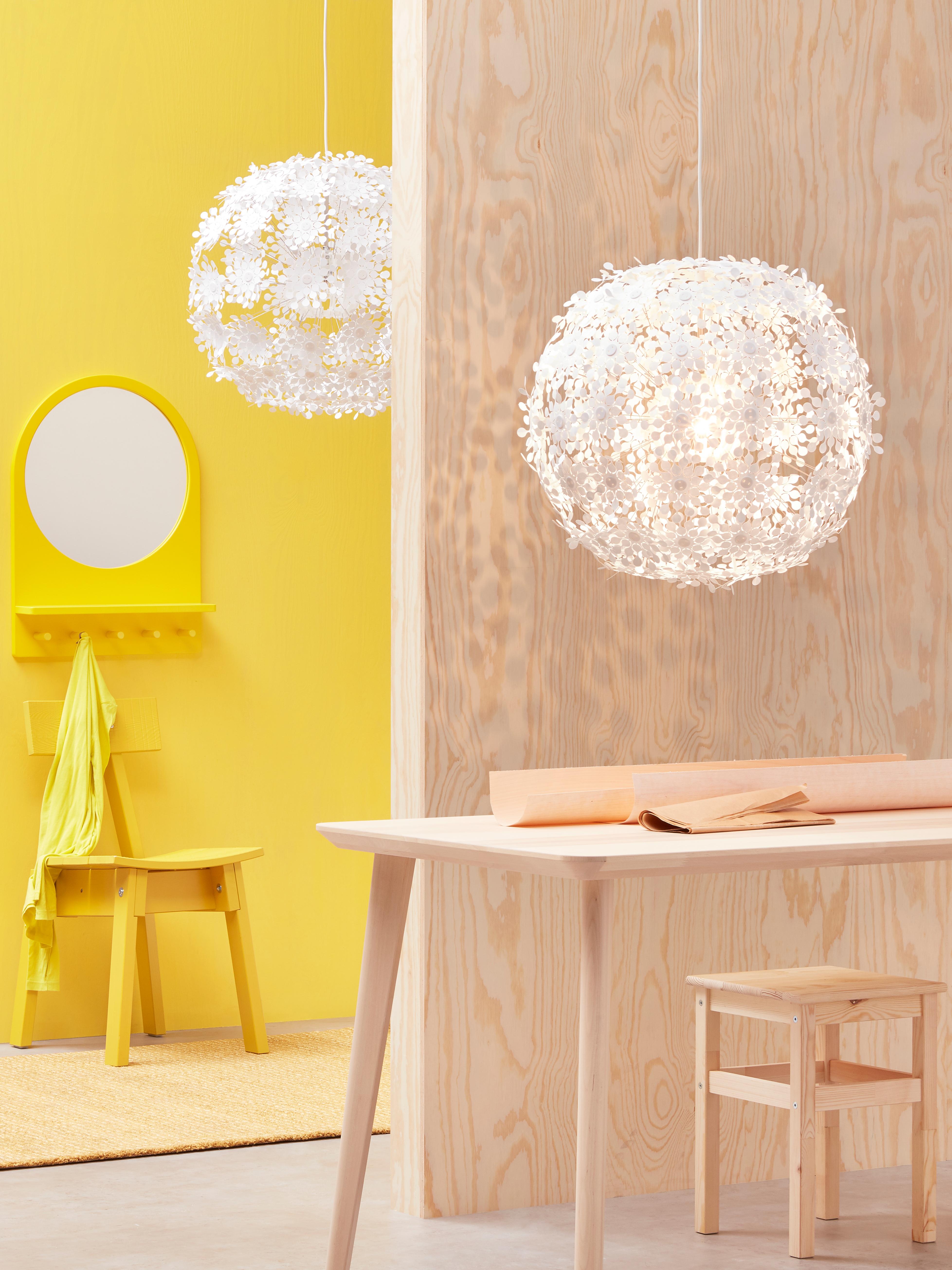 Una postazione di lavoro con un ingresso sullo sfondo; in entrambi gli ambienti c'è una lampada a sospensione GRIMSÅS bianca.