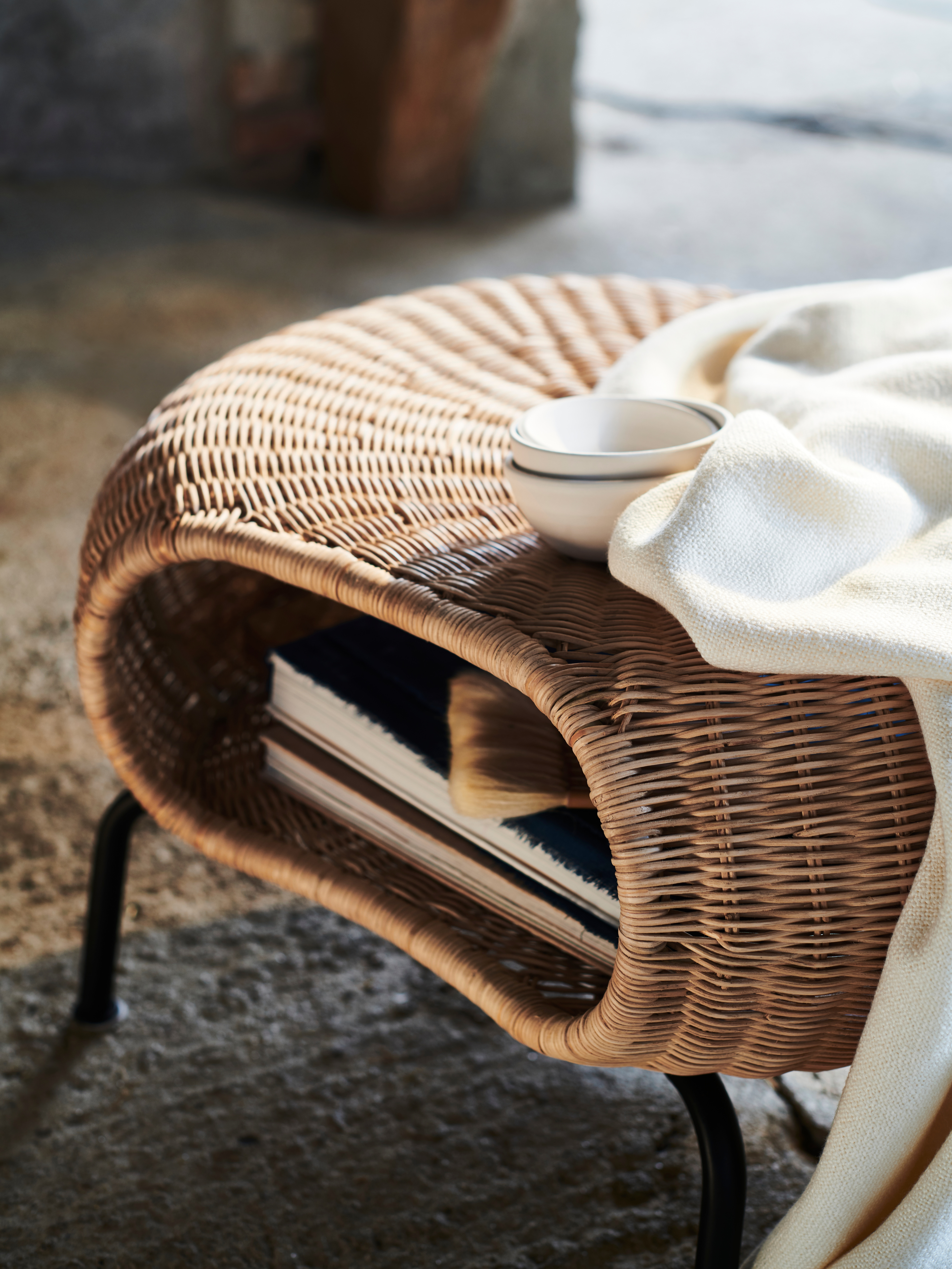 A close-up of a GAMLEHULT footstool with storage in hand-woven rattan with books on the shelf and small dishes on top.