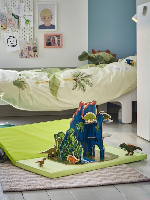 Dinozaurii de jucărie stau pe o saltea pliabilă PLUFSIG de pe podeaua camerei unui copil, cu un pat extensibil SLÄKT în spate.