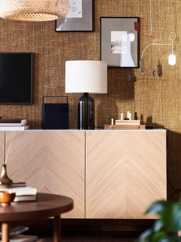 Aparador BESTA em madeira fixo numa parede com textura bege, com candeeiro de abajur branco e coluna em cima.