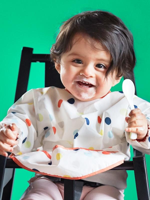 Un copil zâmbitor, cu părul închis la culoare, cu o bavetă KLADDIG și ținând în mână o lingură de plastic, stă pe un scan înalt BLÅMES.