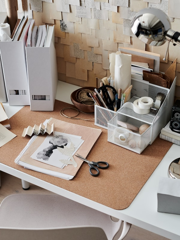 Workspace with a white DRÖNJÖNS organizer, white magazine files, a SUSIG cork desk pad and office paraphernalia.