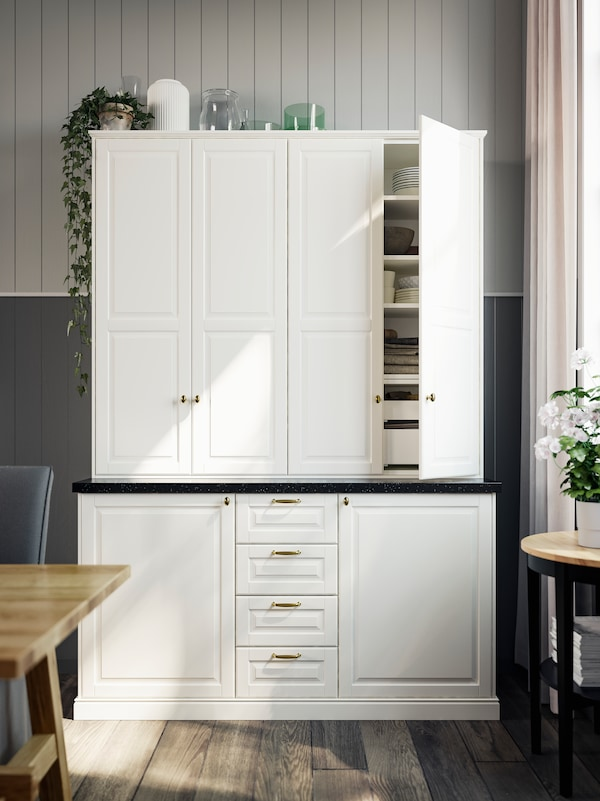 A traditional-looking closed storage unit with white fronts and drawers and brass-coloured handles and knobs.