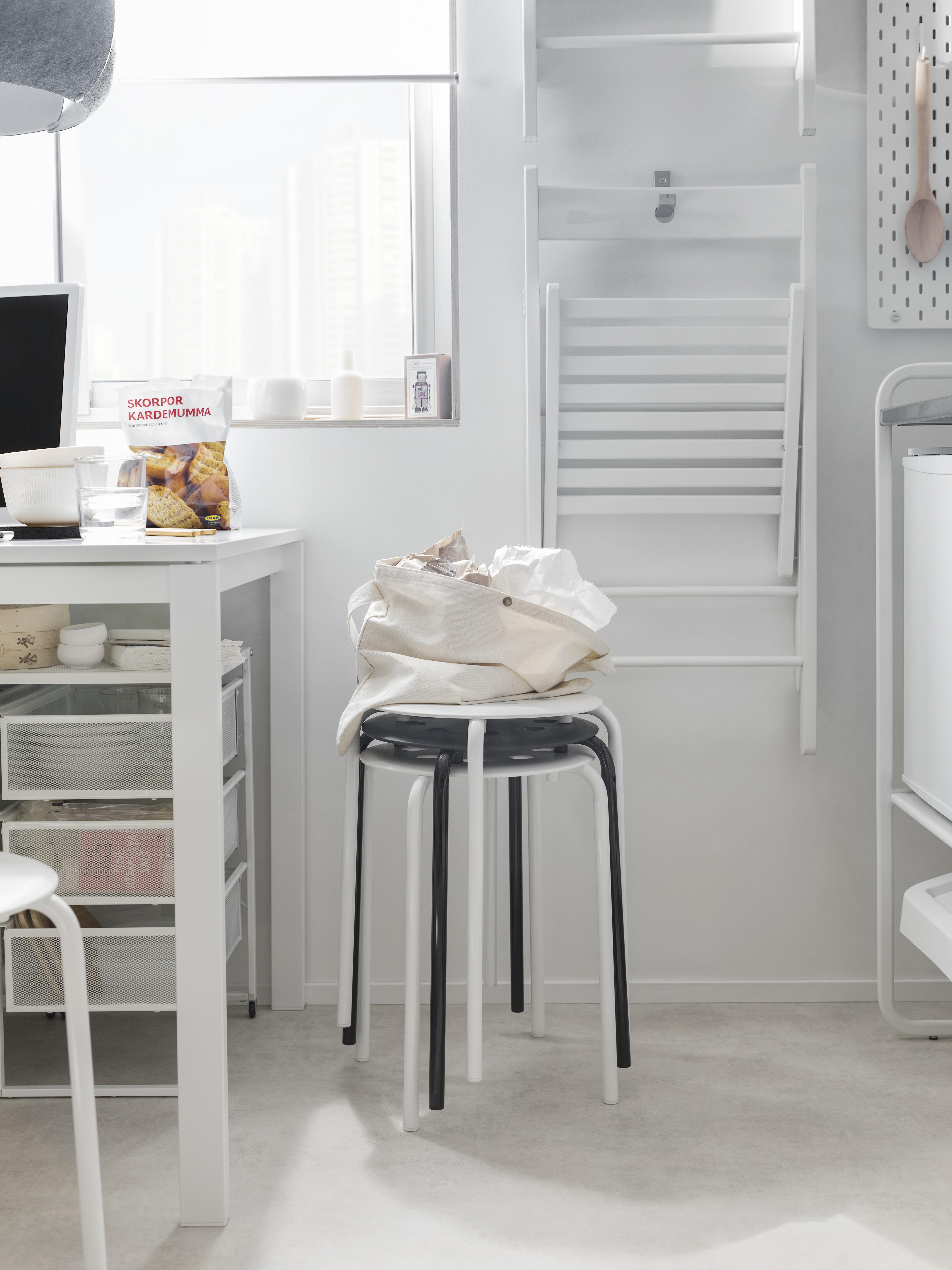 Kuhinjski kutak ima naslagane MARIUS stolce uz bijeli stol i ispred bijelih sklopivih stolica koje vise na zidu.