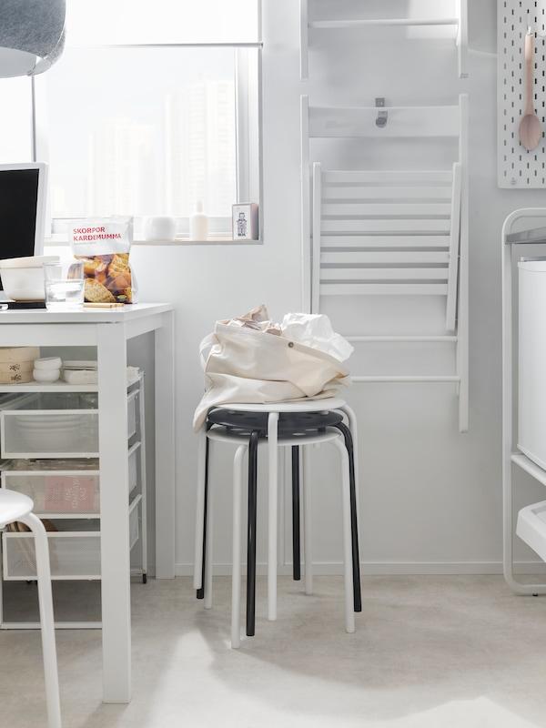 Kuchyňský kout s bílým stolem a bílými skládacími židlemi visícími na zdi a stoličkami naskládanými vpředu.