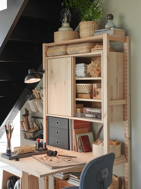 Un rangement en pin avec table pliante sous des escaliers. Des boîtes reposant sur des étagères, dont la minicommode à 3tiroirs PALLRA.