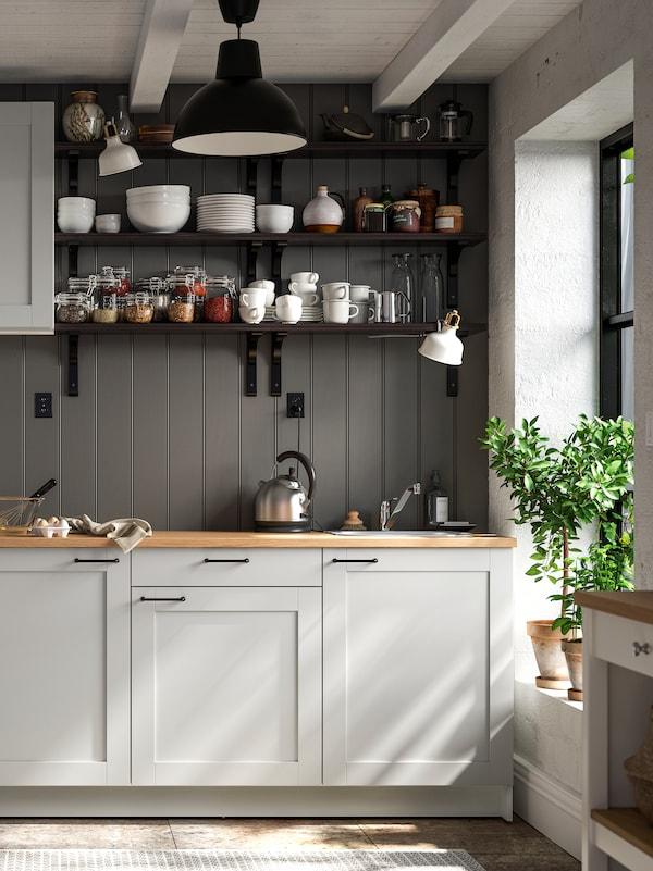 Eine Küche im Landhausstil mit KNOXHULT Schränken vor einer grau getäfelten Wand. Auf Regalen sind Schüsseln, Teller und Dosen mit Deckeln zu sehen.
