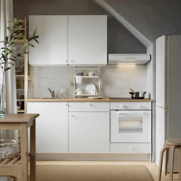 A white KNOXHULT kitchen with wooden worktops, a refrigerator, two stacked stools and a wooden trolley.