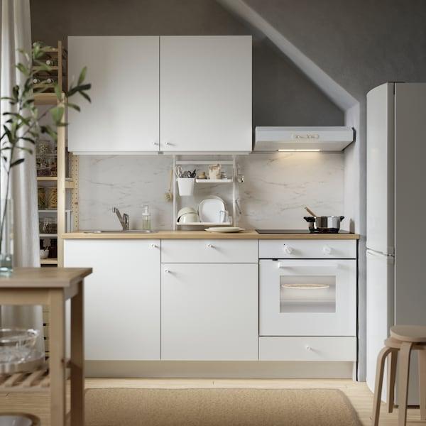 Unha cociña KNOXHULT branca con mesados de madeira, un frigorífico, dous tallos encastelados e un carriño de madeira.