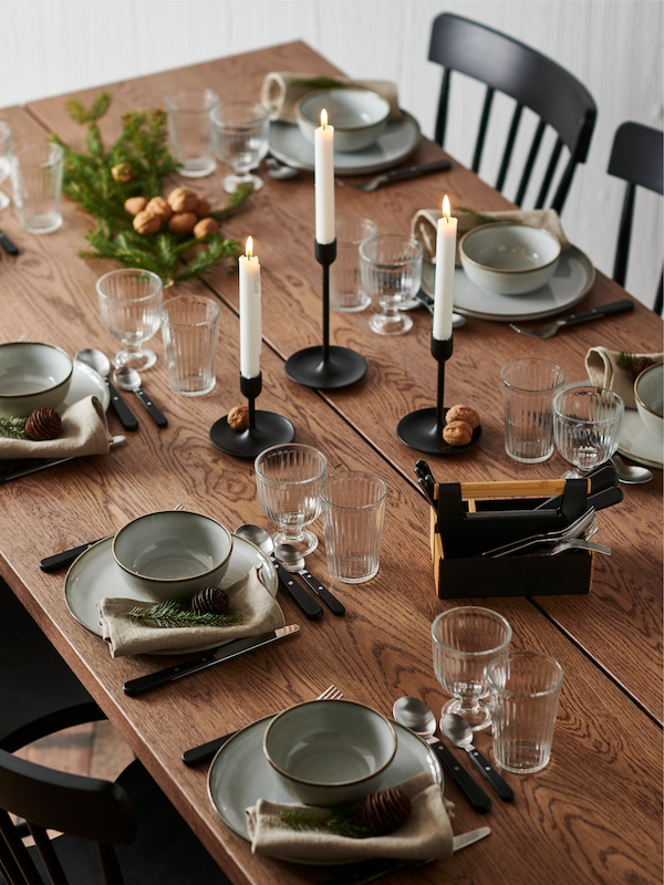 A table set for a celebration with rustic dinnerware, sparkling glasses, black candlesticks and sprigs of greenery.