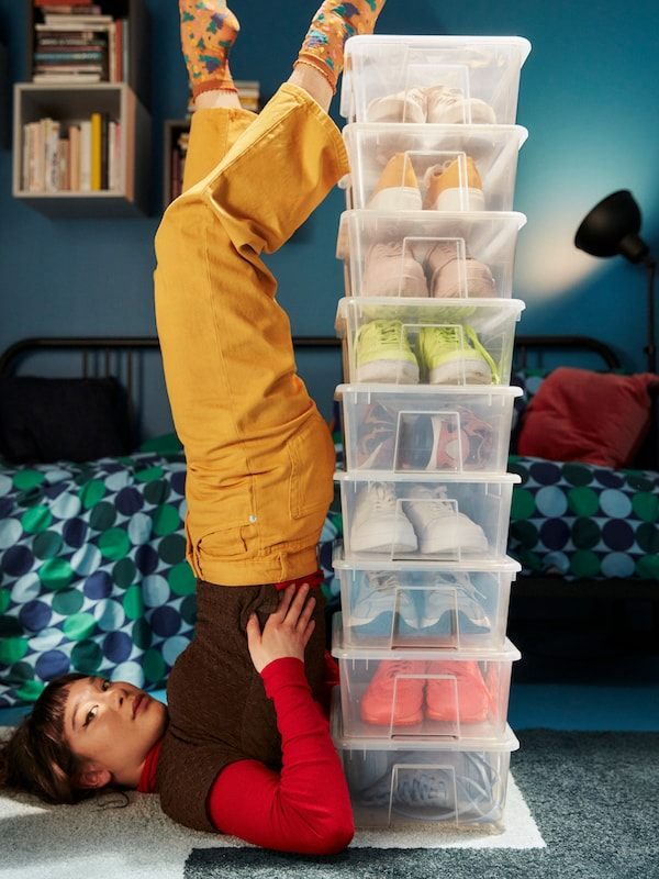 A person lies on the floor with her legs stretching up onto the top of a tower of SAMLA boxes containing trainers.