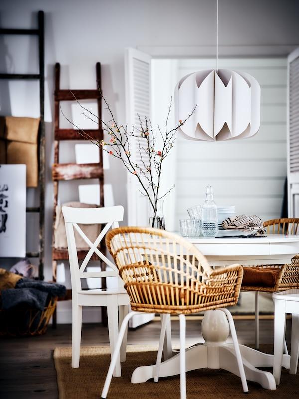Une table blanche entourée d'un mélange de chaises en rotin et en bois, sur laquelle se trouvent de la vaisselle et des verres, dans une salle à manger blanche.