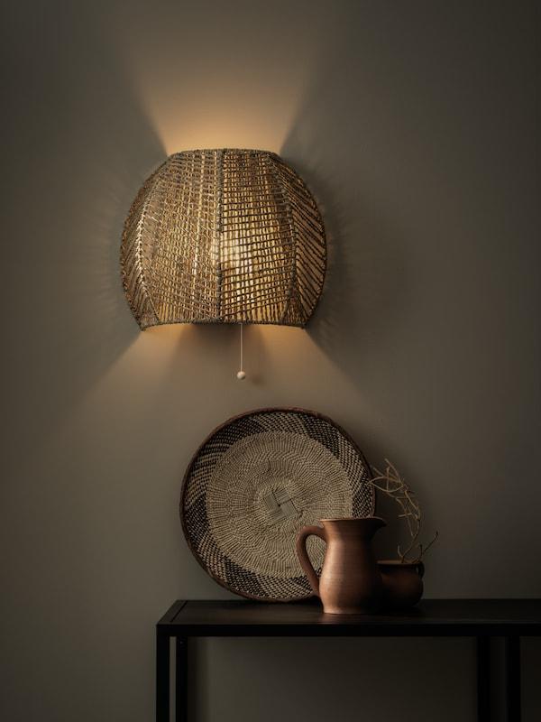 Handgemaakte MÅNALG wandlamp van moerasgras met een tafel tegen de wand met accessoires erop.