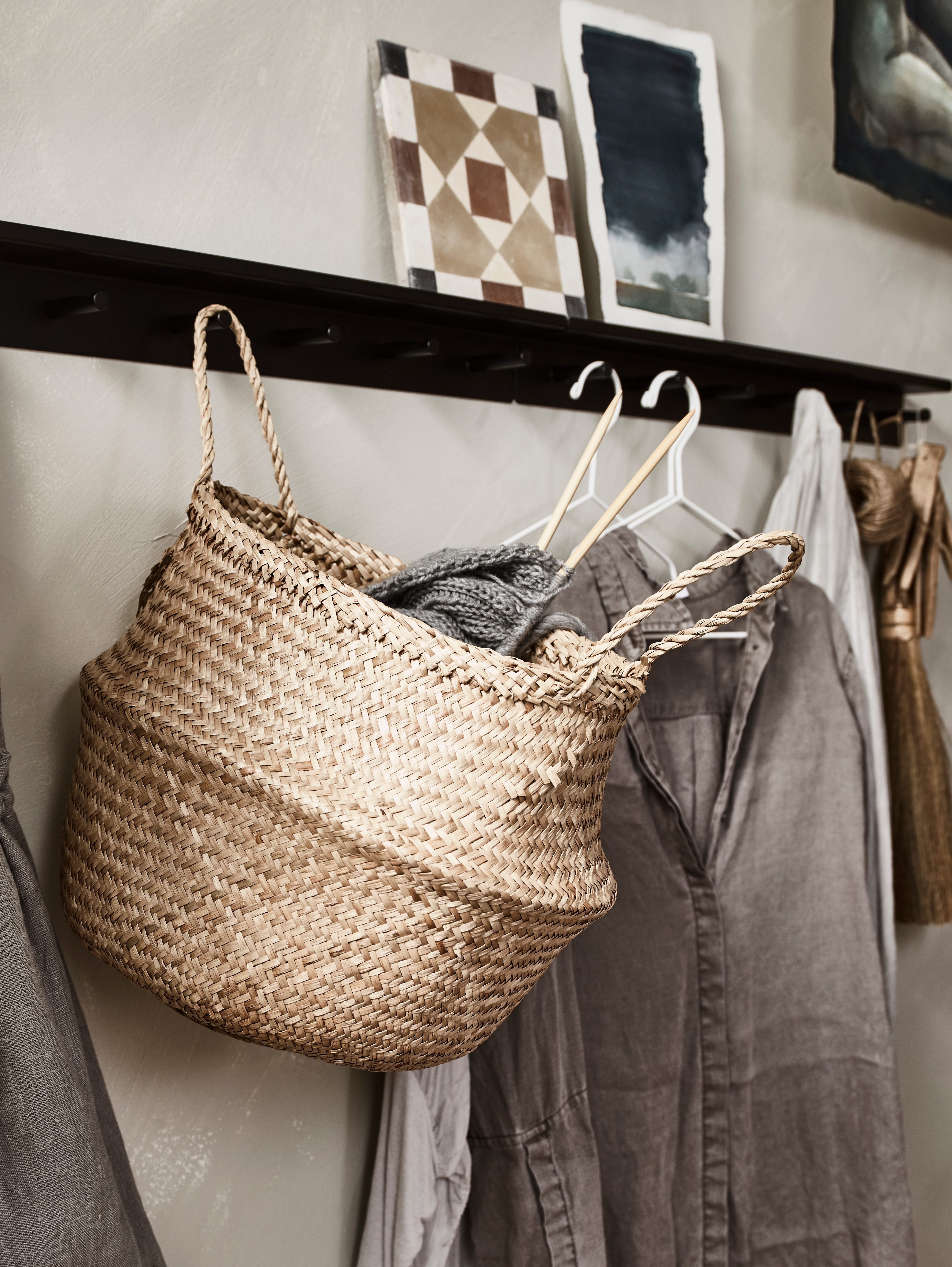 A woven seagrass FLÅDIS basket holds knitting needles and hangs by a handle on a wall rail, beside clothes on hangers.