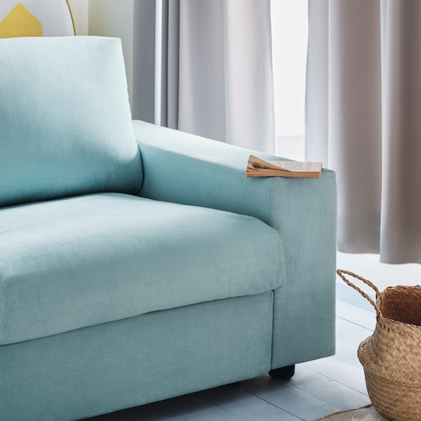 A living room with a light blue VIMLE sofa-bed and beige curtains that are drawn closed.