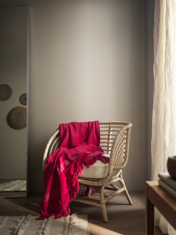 Ręcznie robiona narzuta HILLEGÄRD udrapowana na krześle z naturalnego materiału, stojącym w przytulnym, ciepło oświetlonym rogu pokoju.