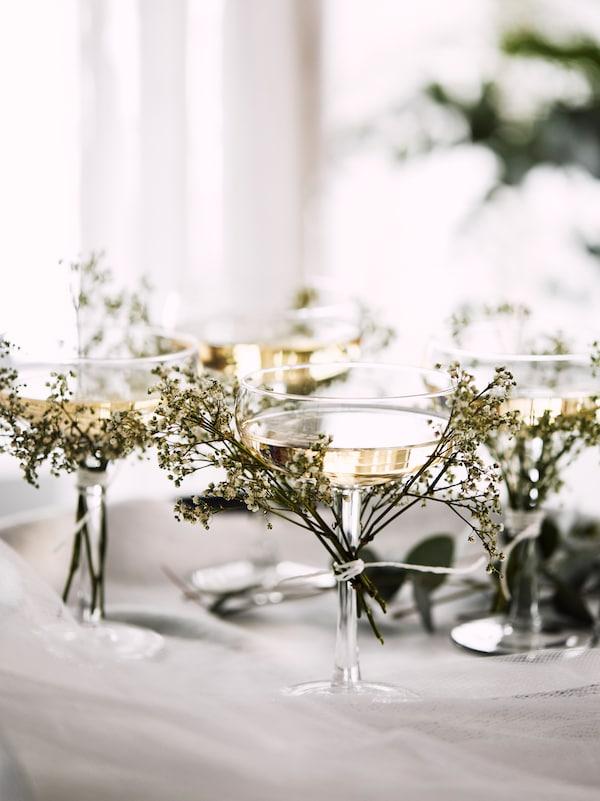 Cuatro copas de champán STORHET sobre una bandeja con ramilletes de flores silvestres atados a los tallos de las copas.