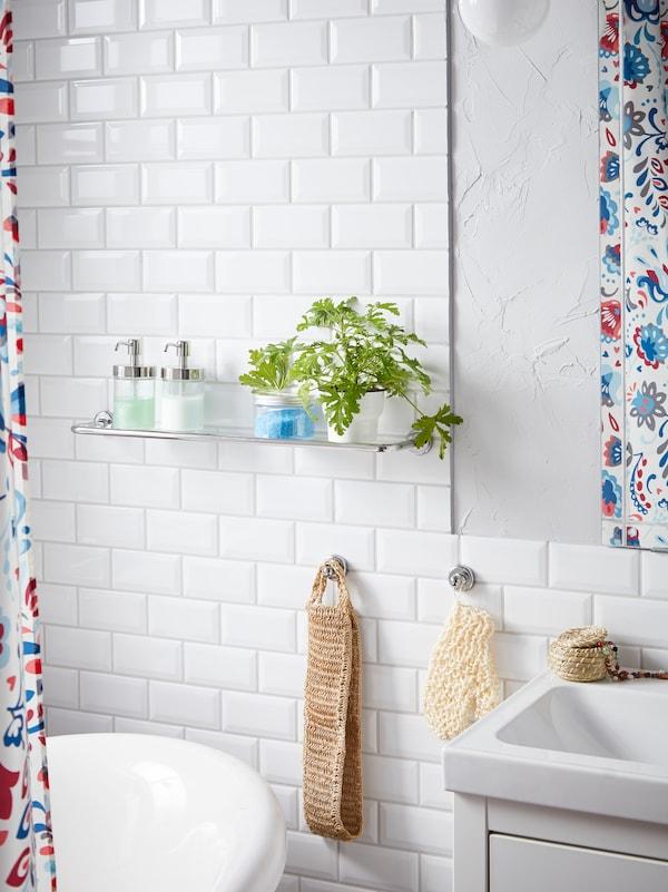 Une étagère en verre VOXNAN à effet chromé, sur laquelle sont disposés du savon et des plantes, est placée à côté de la baignoire et du lavabo.