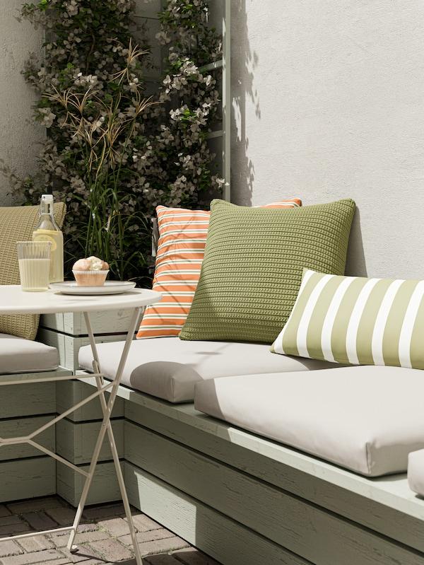 Panca con cuscini sedile beige, cuscini verdi e un cuscino arancione, e tavolo con un cupcake e una limonata.
