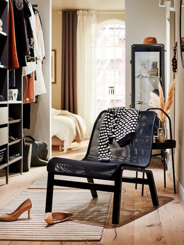 A black NOLMYRA easy chair stands near a wardrobe, with a pair of shoes in front of it and a cardigan draped over the back.