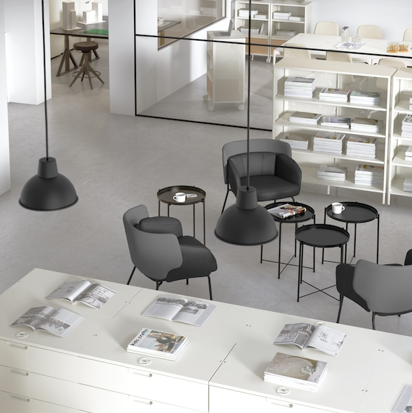 An office with black coffee tables and chairs, white storage units with various items on them, and hanging lighting.