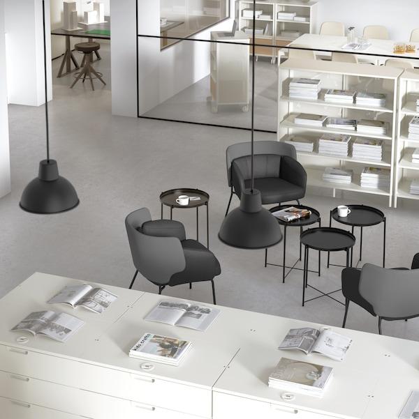 Pisarna s črnimi klubskimi mizami in stoli, belimi enotami za shranjevanje, na katerih so različni predmeti, viseča svetila.